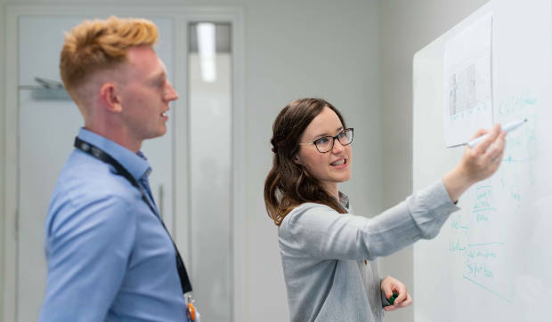 man and woman collaborating on a whiteboard